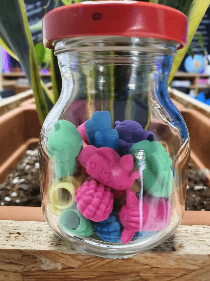 Frasco con borradores de colores para lápices